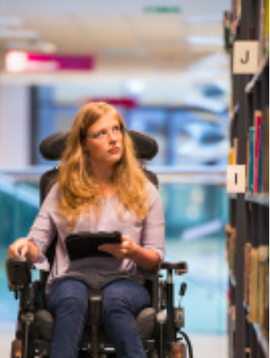 A woman in a wheelchair peruses books at her local library